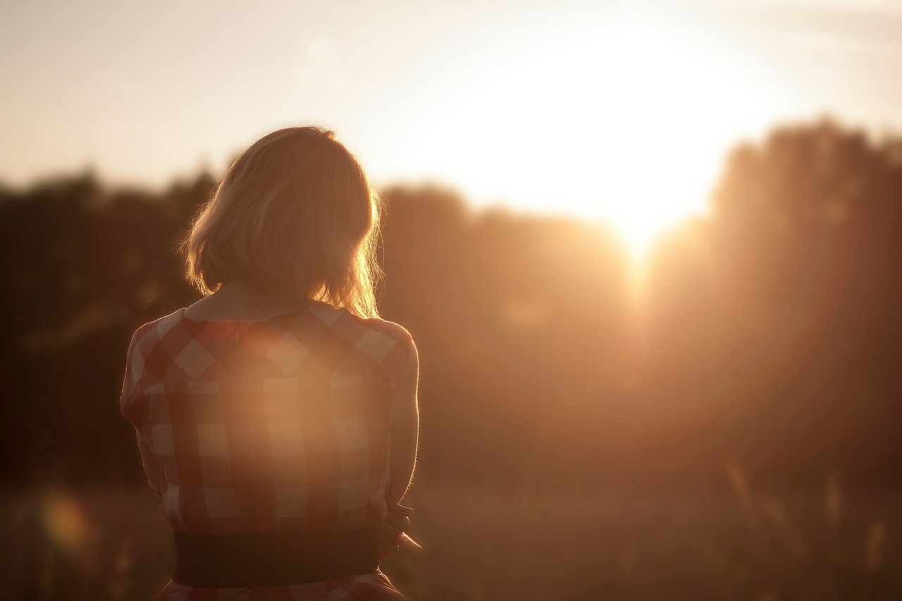 Lonely picture of a girl in a flannel shirt from behind staring into a bright sunset. The space next to her is unoccupied.