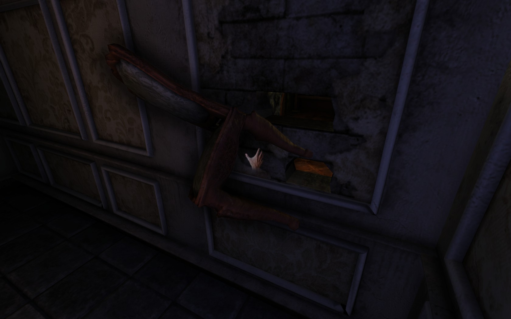 A chair is stuck to a crumbling wall.