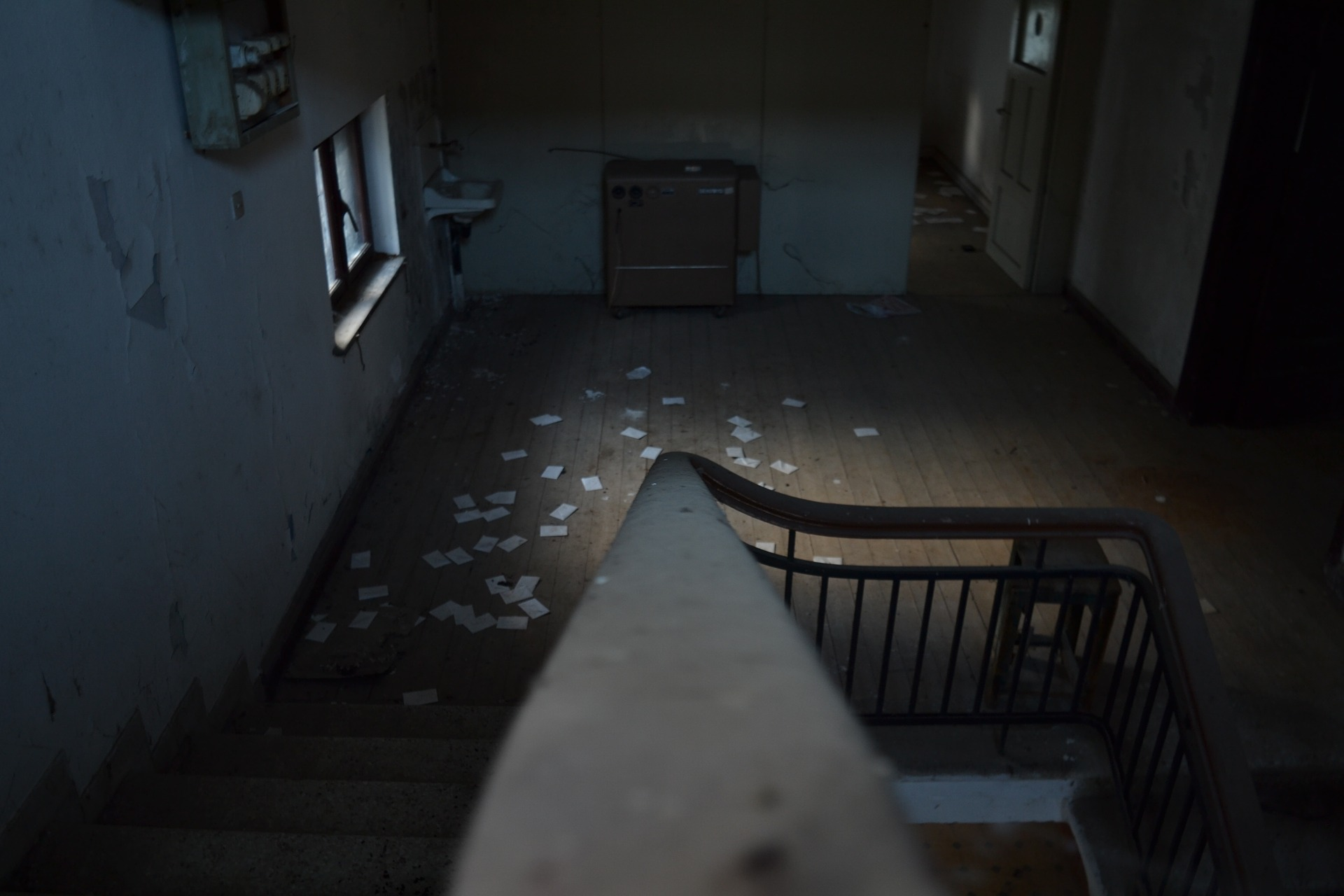 An abandoned house, seen from above on the bannister. Paper litters a dark, empty room.