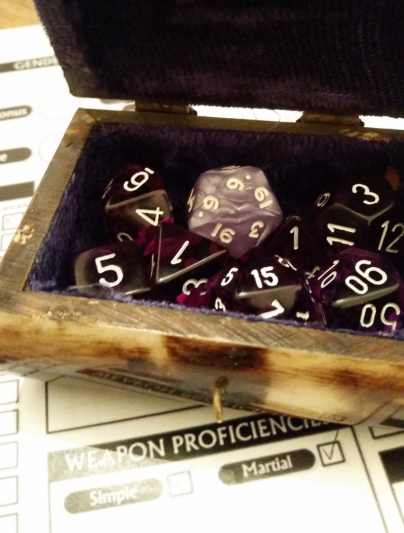 A purple set of dice used for Dungeons & Dragons: a D4, D6, D8, D10, D12, and D20 arrayed like treasure in a chest.