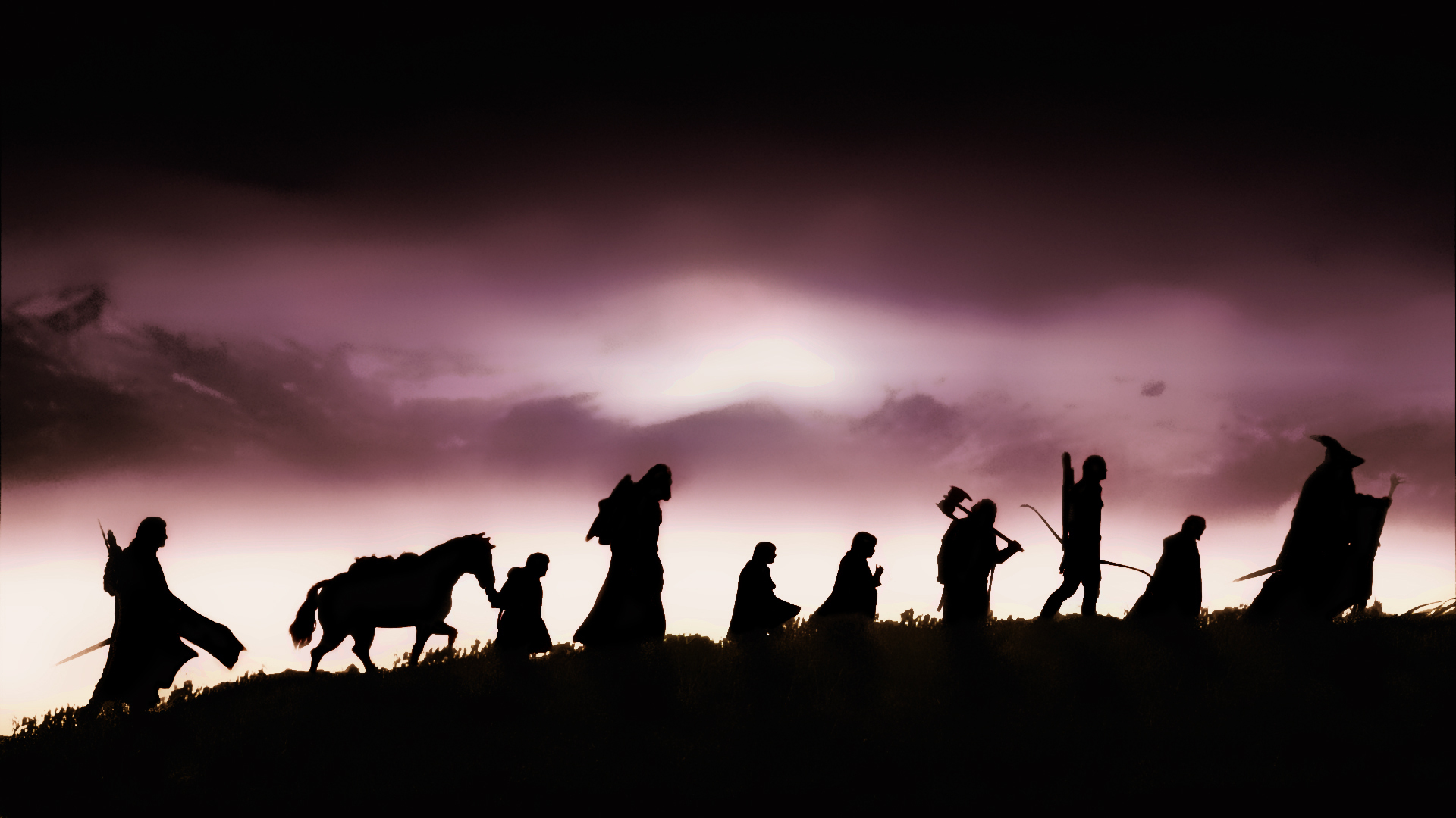 The cast of The Fellowship of the Rings, silhouetted against a cloudy, purple sky.