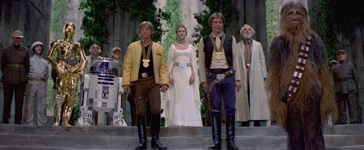 The medal ceremony at the end of Star Wars: A New Hope. Luke, Han, and Chewie stand on a podium. Leia, R2D2, and C3PO an various important-looking people stand behind them.
