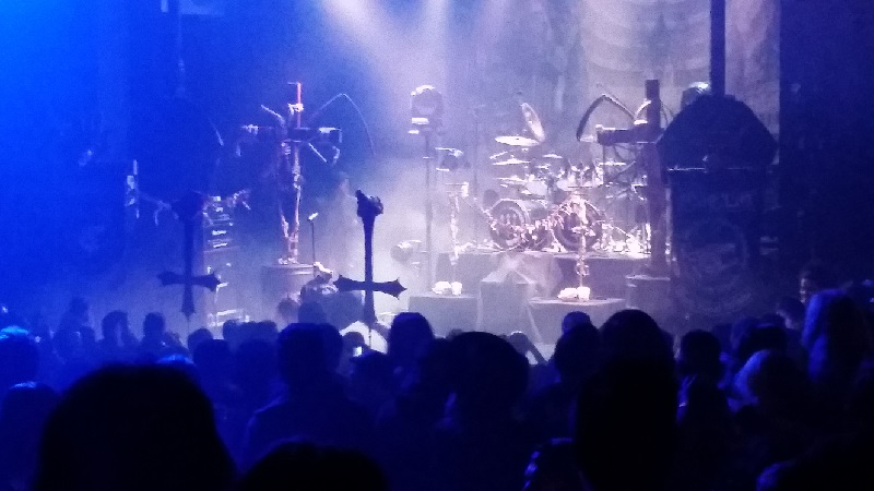 Watain's stage. Upside-down crosses, mock crucifixes (complete with skeletons and scythes), and ritual prayer candles can be seen through the haze.