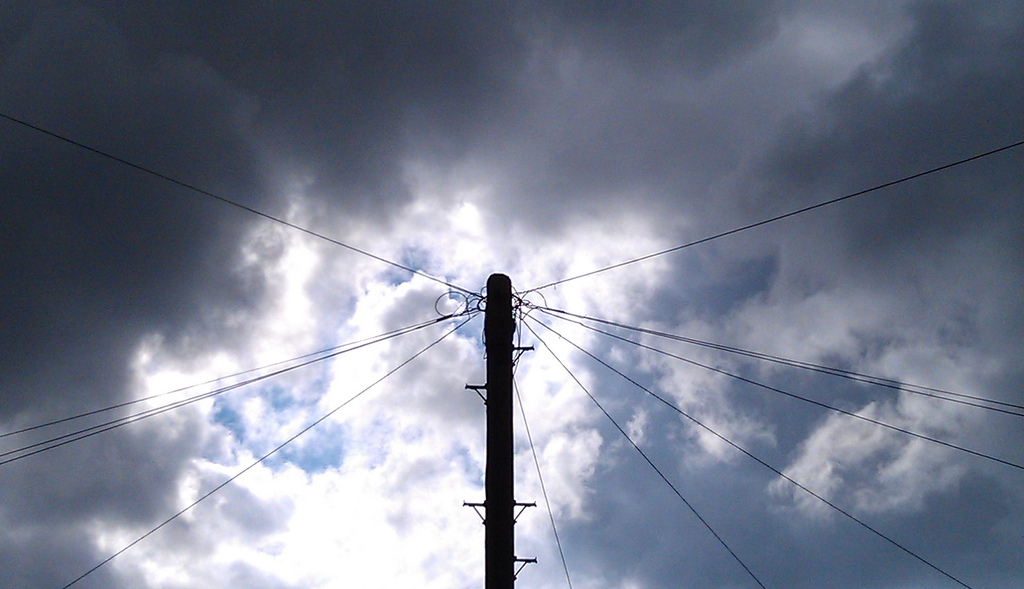 A telegraph pole with wires pointing out from it like spokes in a wheel rises into a cloudy sky.