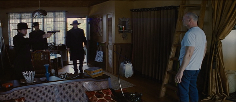Three men in black coats and wide-brimmed hats enter Joe's home. One points a long-barreled gun at Joe, who stands off to the right.