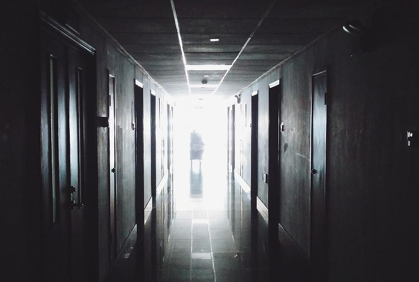 A dark hospital corridor leads to a blinding white end of the hallway. A shadowy figure awaits at its end.