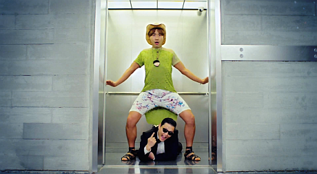 "Screenshot from the viral video ""Gangnam Style,"" in which singer PSY lies on the floor of an elevator and a colorfully dressed man dances over him."