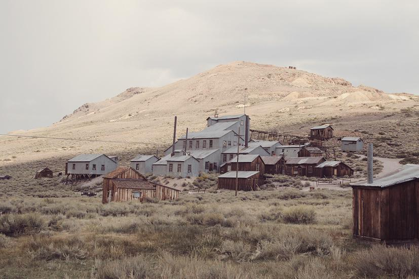 A ghost town nestled in some dry hills.