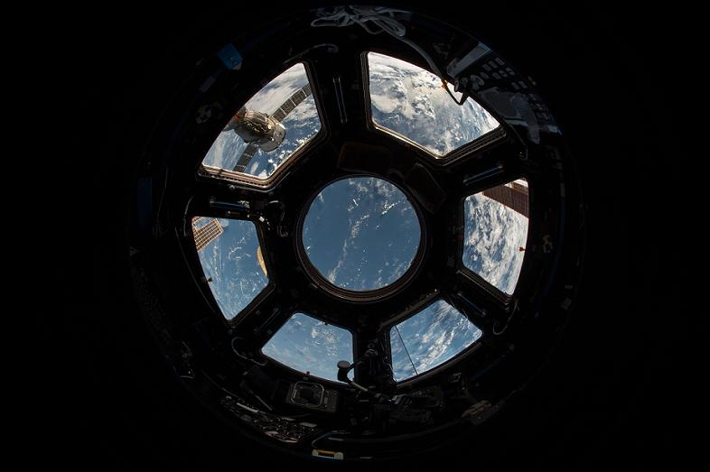 Through the window of a spaceship cockpit, Earth is seen below.